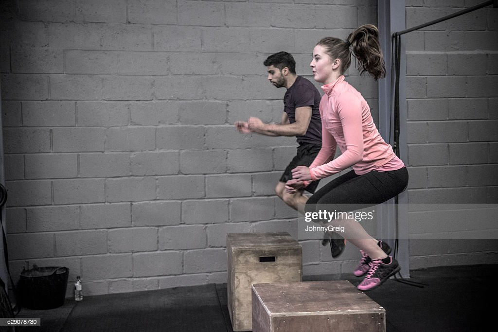 Two people doing box jumps in cross training class. : Stock Photo