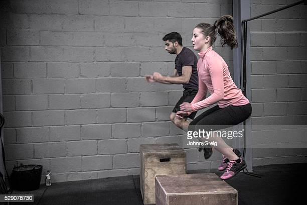 two people doing box jumps in cross training class. - circuit training stock photos and pictures