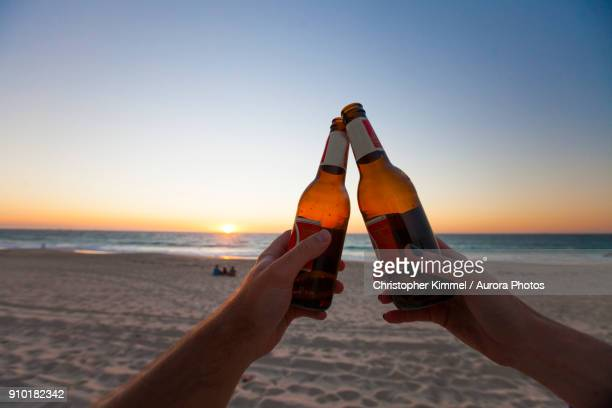 two people doing celebratory toast with beer bottles on beach at sunset, perth, western australia, australia - toost stockfoto's en -beelden
