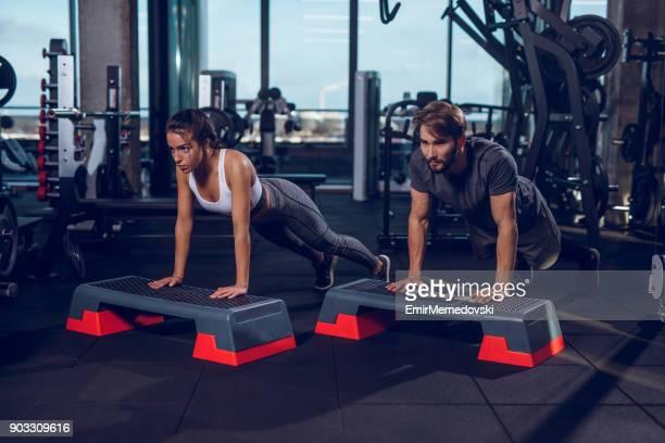 Deux personnes de faire des tractions sur l'équipement d'aérobic d'étape