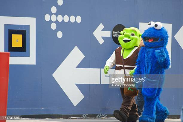 Two people dressed in costumes one a blue monster one shrek walking in front of blue wall in midtown, manhattan, new york city
