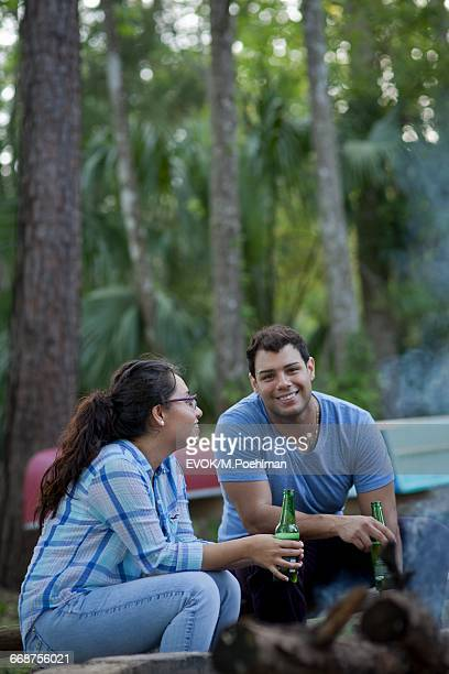 Two people drinking beer by campfire