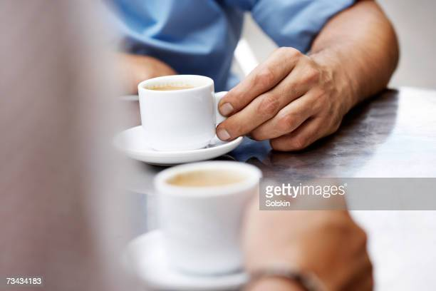 Two people drinking espresso at outdoor cafe, close-up of hands