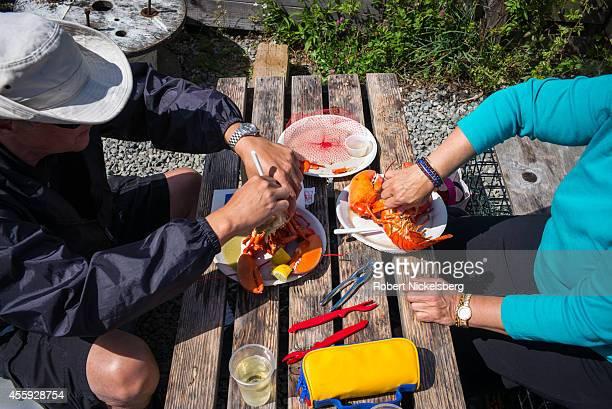 Two people eat fresh lobsters outside of a seafood restaurant on Martha's Vineyard September 13 2014 in Menemsha Massachusetts