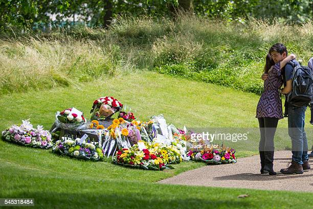 Two people embrace as survivors friends and relatives of the victims of the London bombings lay flowers at the 7/7 memorial on July 7 2016 in London...