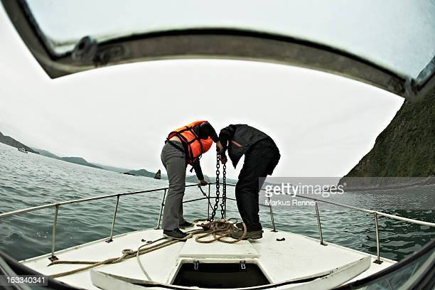 Two people engaged in lowering an anchor off the bow of a boat, Avacha Bay, Russia