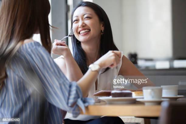 明るい日光の下でコーヒーとケーキを楽しんでいる二人。