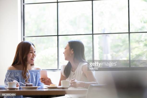Two people enjoying coffee and cake in bright sunlight.