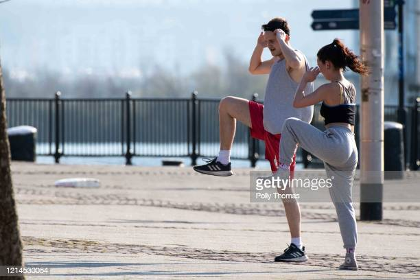 Two people exercise outside in Cardiff Bay on March 24 2020 in Cardiff United Kingdom British Prime Minister Boris Johnson announced strict lockdown...