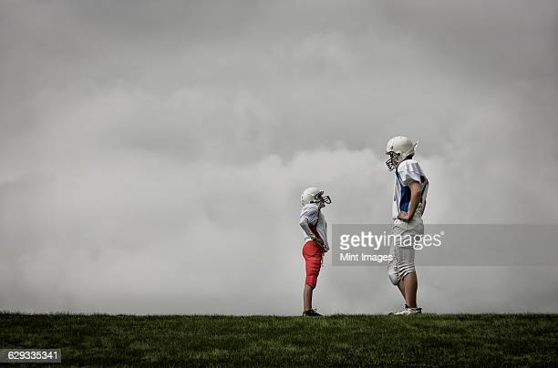 Two people facing each other, one very tall football player, and one much shorter person looking up, hands on hips.