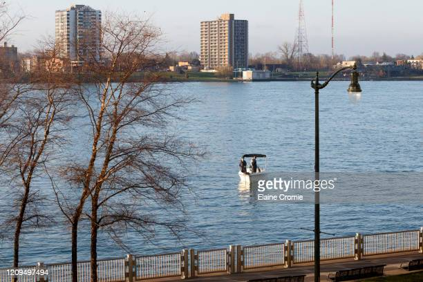Two people fish from a boat on the Detroit River across from Windsor, Ontario, Canada on April 8, 2020 in Detroit, Michigan. In an effort to slow the...