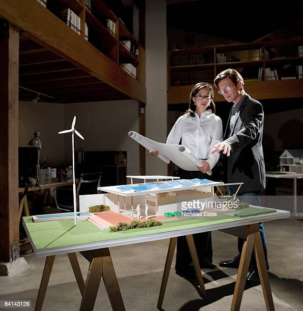 Two people go over plans and architectural model.
