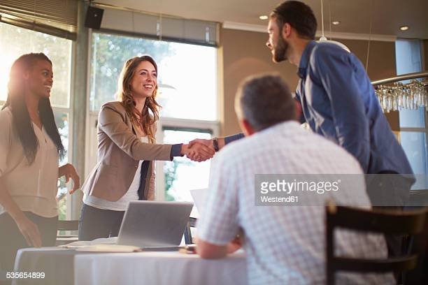 Two people greeting each other at a business meeting in a restaurant keywords m4hsunfo