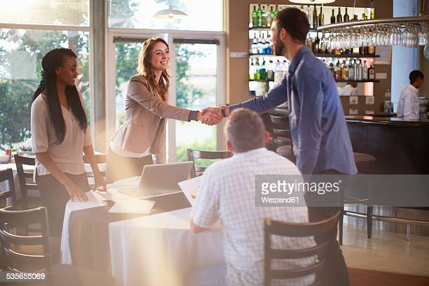 Two people greeting each other at a business meeting in a restaurant