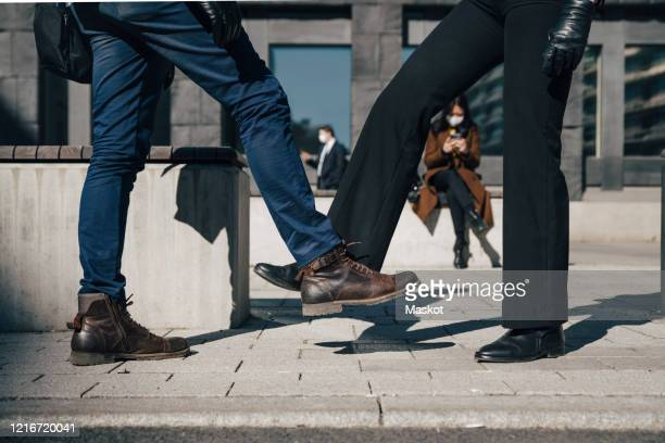 two people greeting with feet during pandemic - avoidance stock pictures, royalty-free photos & images