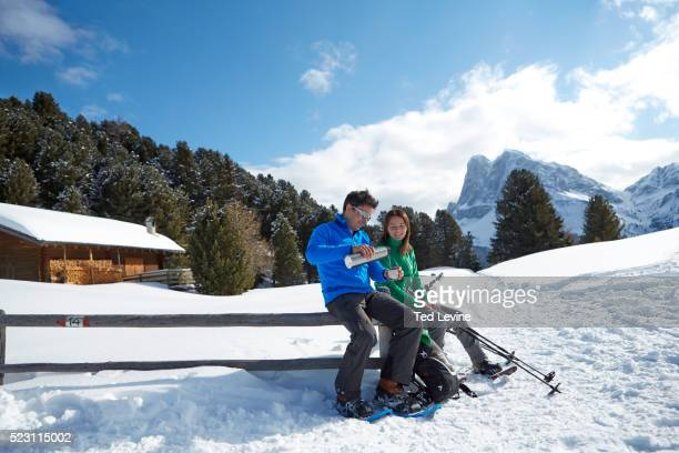 Two people having break during snowshoeing in Dolomites, Schatzer Hut, Eisacktal, South Tyrol, Italy
