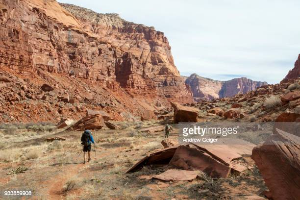 Two people hiking along trail across landscape in red rock desert canyon environment.