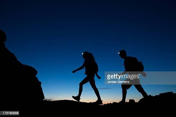 Two people hiking at night.