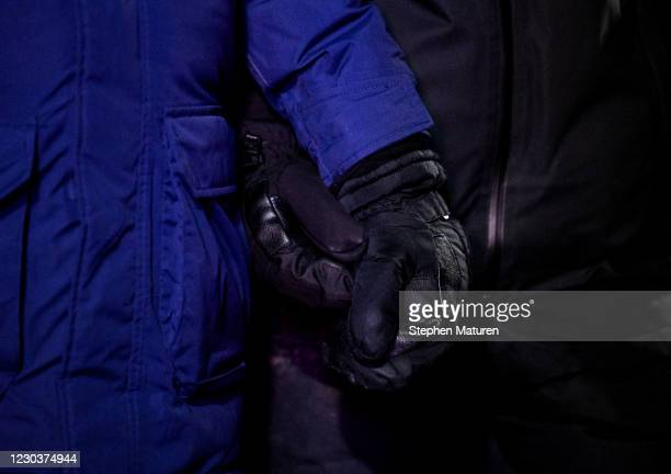 Two people hold hands through their gloves during a vigil for Dolal Idd, who was shot and killed by Minneapolis Police last night, on December 31,...