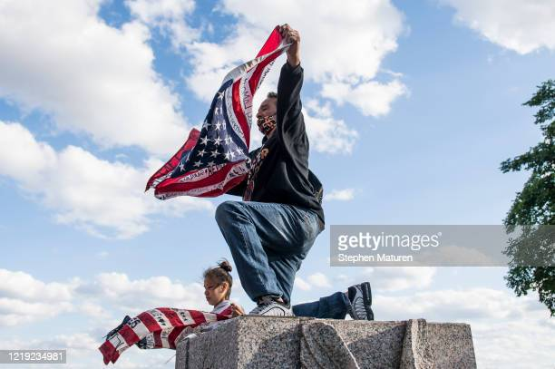 Two people hold up flags noting the names of Native American people who have been killed on the spot where a statue of Christopher Columbus which was...