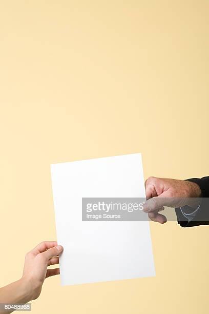 two people holding a paper - passeren stockfoto's en -beelden