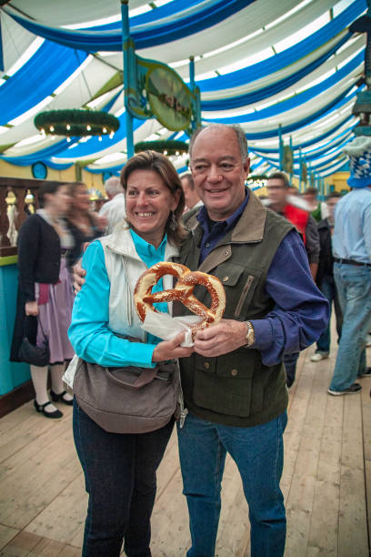 Two people holding a pretzel inside one of the Tents at the oktoberfest