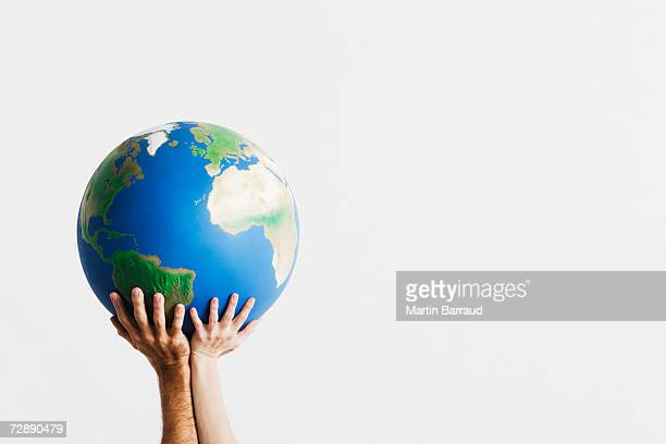 Two people holding globe in raised hands against white background,close-up