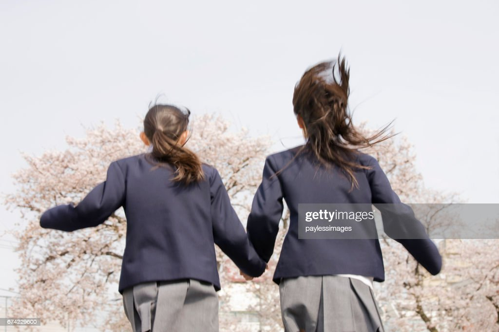 Two people holding hands, runs women's junior high school students : Stock Photo