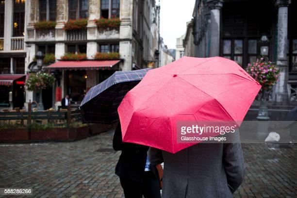 two people holding umbrellas in rain, brussels, belgium - regen stockfoto's en -beelden