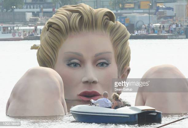 Two people in a boat approach Die Badende a giant sculpture showing a woman's head and knees as if she were resting in the Binnenalster lake on...
