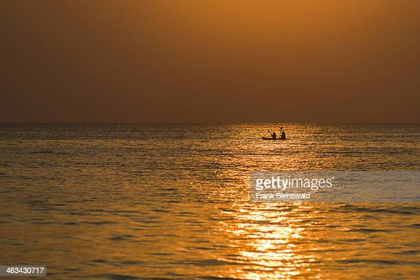 Two people in a kayak are canoeing in the open sea at sunset at Palolem Beach