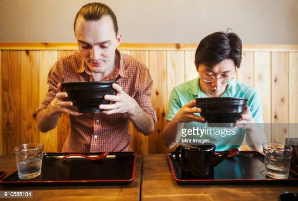 two people in a noodle cafe lifting bowls of soba noodles. a western man and a japanese man. - soba stock pictures, royalty-free photos & images