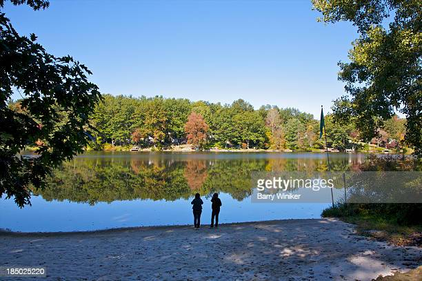 Two people in front of calm waters in fall