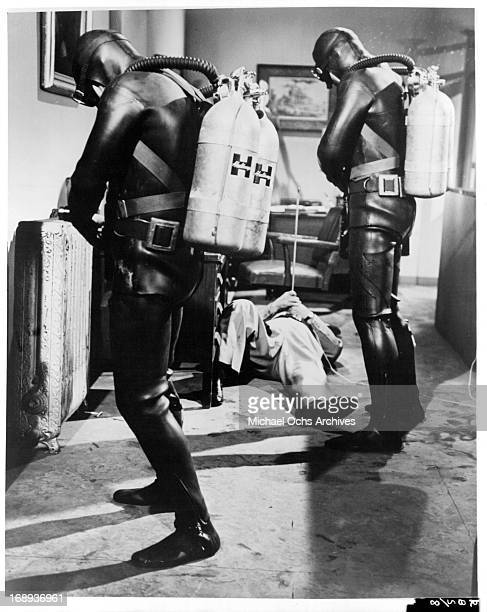 Two people in full scuba diving gear standing in a room with a man laying on the floor injured from the spear stuck in his stomach in a scene from...