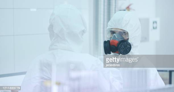 two people in lab wearing protective suits are talking - biochemical weapon stock pictures, royalty-free photos & images