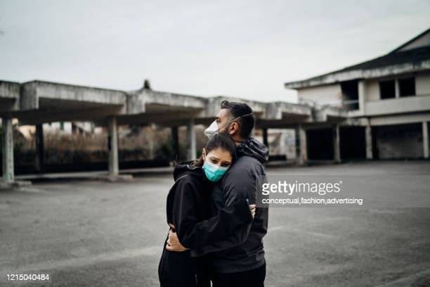 two people in masks hugging.couple being divided by incurable infectious disease.infection control,isolation.loved one illness.saying goodbye.farewell.letting go.toxic relationship. - hepatitis stock pictures, royalty-free photos & images