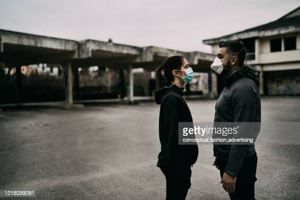 two people in masks talking from distance.couple being divided by incurable infectious disease.infection control,isolation.loved one illness.saying goodbye.farewell.toxic relationship. - aids stock pictures, royalty-free photos & images