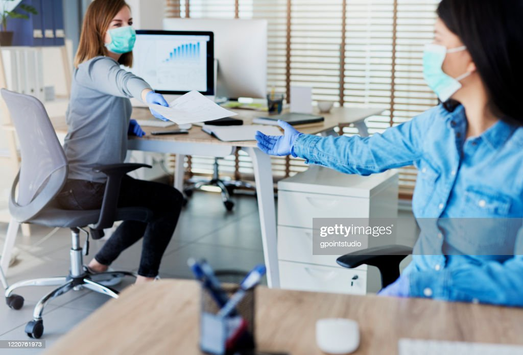 Two people in office passing documents with keeping a distance : Stock Photo