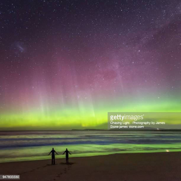 Two people in silhouette dancing on a beach under the aurora australis