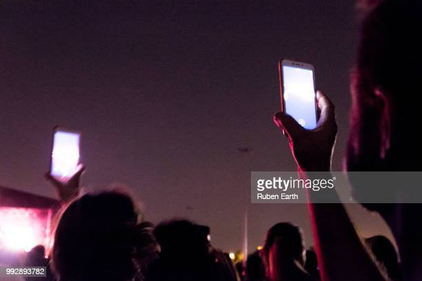 two people in the public rising the mobile phone - pop music stock pictures, royalty-free photos & images