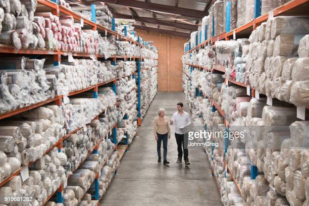 two people in warehouse with carpets on shelves high angle view - man wrapped in plastic stock pictures, royalty-free photos & images
