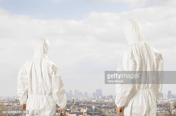two people in white suits looking at cityscape, rear view - biochemical weapon stock pictures, royalty-free photos & images
