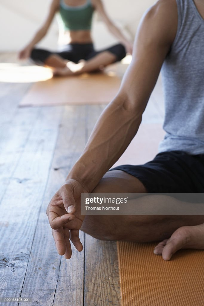 Two people in yoga class, low section (focus on man meditating) : Stock Photo