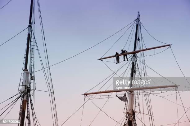 two people inspect boom on sailboat - tuig mast stockfoto's en -beelden