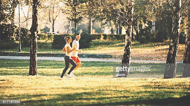 Two people jogging in park.