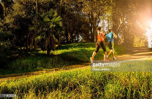 Two people jogging on forest path