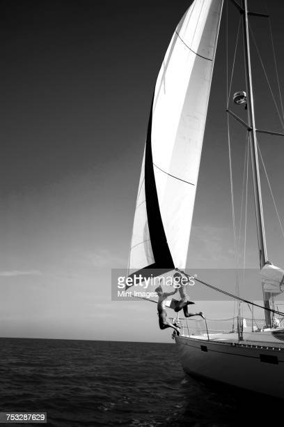 two people jumping from a yacht into the ocean. - voilier noir et blanc photos et images de collection