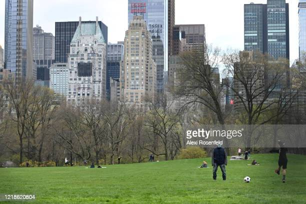 Two people kick a soccer ball around in Sheep Meadow Central Park amid the coronavirus pandemic on April 12 2020 in New York City United States...