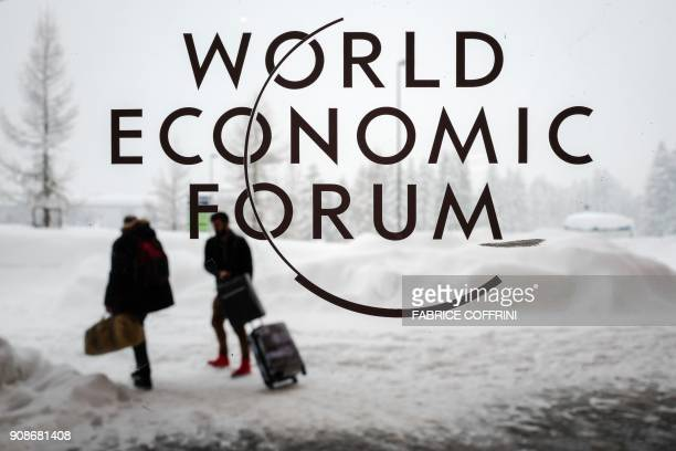 Two people leave the Congress Centre under snow ahead of the opening of the World Economic Forum 2018 annual meeting on January 22 2018 in Davos...