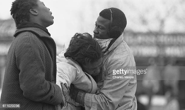 Two people lift the unconscious body of Civil Rights activist Amelia Boynton at the base of the Edmund Pettus Bridge during the first Selma to...